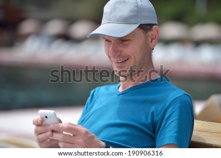 Man with smartphone on a beach - stock photo