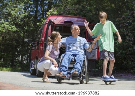 Man with spinal cord injury in a wheelchair with family near his adaptive van with teenager on a skateboard - stock photo