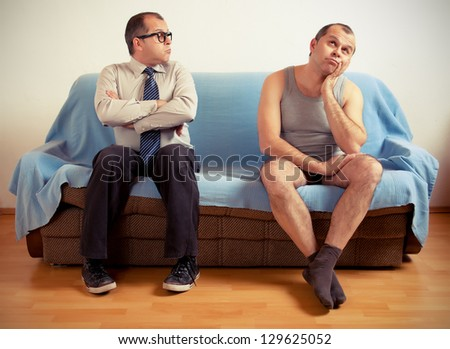Man with split personality sitting on a couch - stock photo