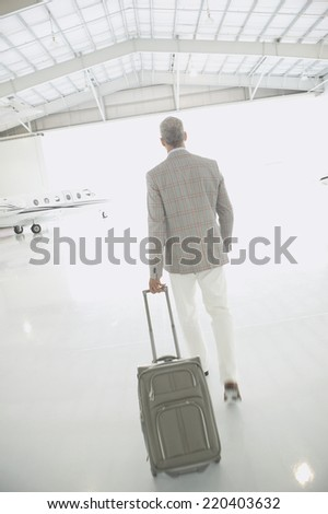 Man with suitcase walking out of airplane hanger - stock photo