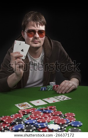 Man with sun glasses playing poker on green table. Chips and cards on the table.