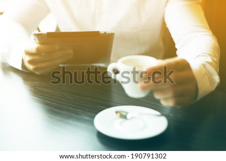 Man with tablet computer and coffee reading news at motning in cafe shop - stock photo