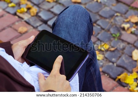 Man with tablet computer at work, sitting in the autumn park on a bench