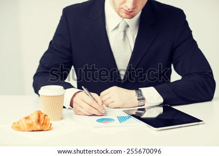man with tablet pc and cup of coffee writing something - stock photo