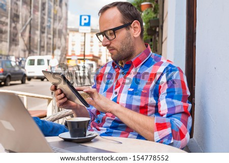 Man with tablet pc in cafe. He is drinking coffee. - stock photo