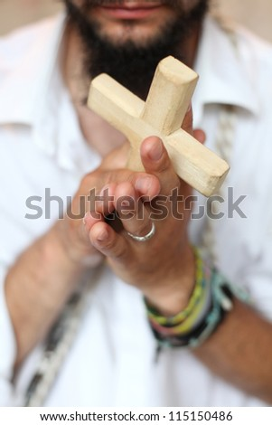 Man with the cross in hands - stock photo