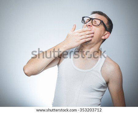 Man with their hand over his mouth yawning, sleepy funny guy in undershirt against gray backround