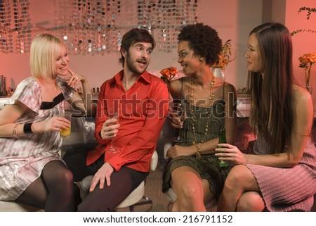 Man with three girls at a nightclub. - stock photo