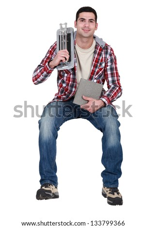 Man with tile cutter sat on ledge - stock photo