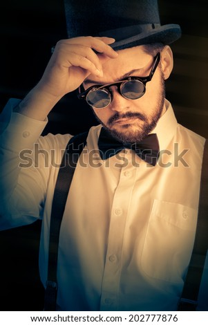 Man with Top Hat and Steampunk Glasses Retro Portrait - Gentleman portrait, young bearded man wearing steampunk glasses, bowtie and top hat  - stock photo