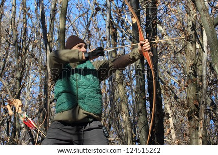 man with traditional longbow in a winter shot - stock photo