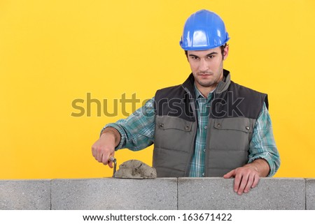 Man with trowel spreading cement on wall - stock photo