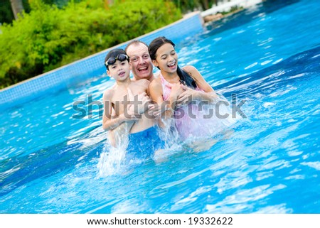 Man with two children enjoying the swimming pool - stock photo