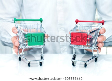 Man with two miniature trolleys. Conception of making a choice when shopping. - stock photo