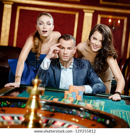 Man with two women playing roulette at the casino. Addiction to the gambling - stock photo