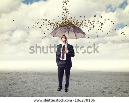 man with umbrella and coin rain - stock photo