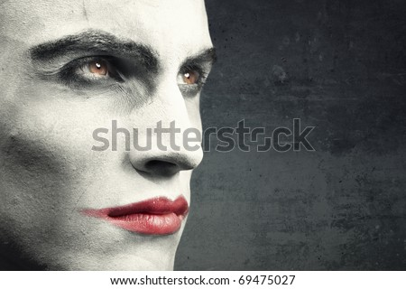Man with vampire makeup on a dark grungy background. Natural makeup and background. Text can be added onto the empty space - stock photo