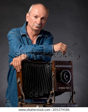 Man with vintage wooden photo camera on a dark background - stock photo