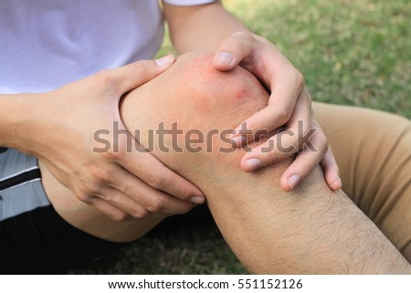 man with whit t-shirt and black short trousers with knee pain in an Elastic Bandage sit on the green grass /two hands touch his red knee