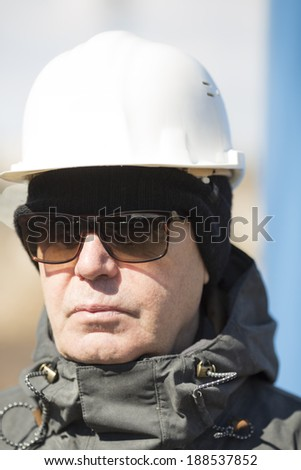 man with white hardhat and sunglasses - stock photo