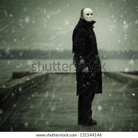 man with white mask near the river and snow - stock photo