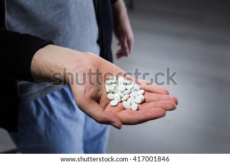 Man with white pills in hand