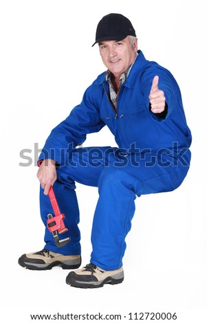Man with wrench sat giving the thumbs-up - stock photo