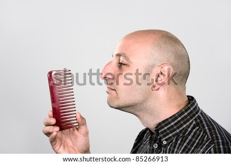 man without hair is looking to the comb - stock photo