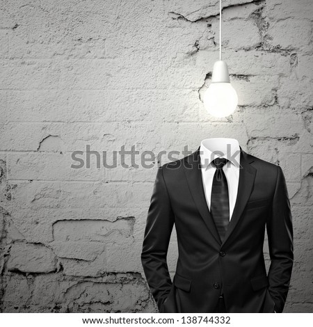 Man without head and  with bulb above - stock photo
