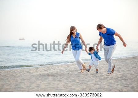 Man woman and child run on the beach near the ocean and feel happy - stock photo
