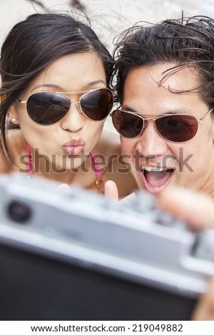 Man & woman Asian couple, boyfriend girlfriend in bikini, taking vacation selfie photograph at the beach  - stock photo