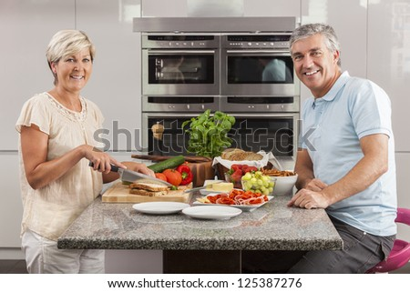 Man & woman couple preparing fresh healthy sandwiches in home kitchen with ham, cheese, salad lettuce and tomatoes - stock photo