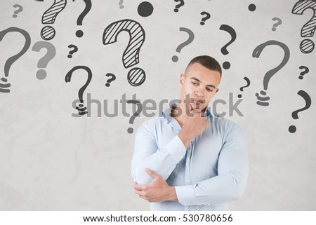 Man wondering with question marks around him