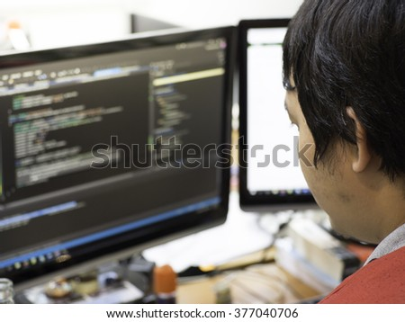 Man work in a programming code with casual clothes, screen on messy desk
