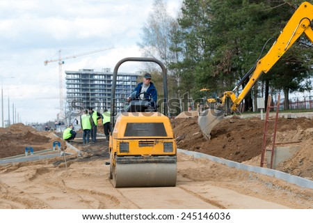 Man worker compacting soil with vibroroller machine during city road construction works crews - stock photo