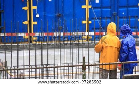 man worker construction building in rain - stock photo