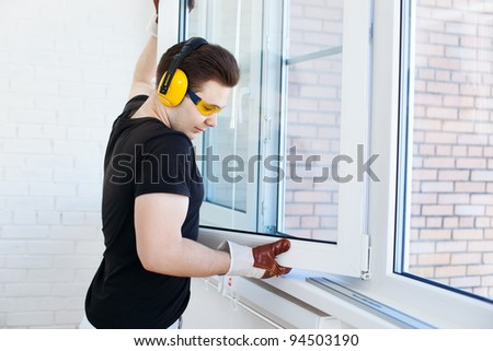 Man worker mounting window on balcony. - stock photo