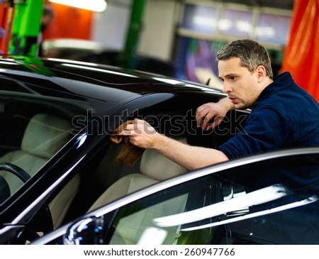 Man worker polishing car on a car wash  - stock photo