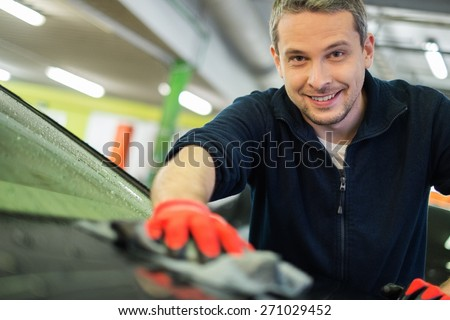 Man worker wiping car on a car wash  - stock photo
