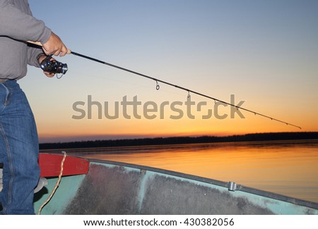 Man working a spinning reel as the sun is going away in Saskatchewan Canada