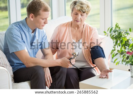 Man working as a nurse taking blood pressure - stock photo