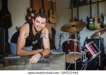 Man working as seller in a music store - stock photo
