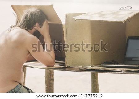 Man working at a computer standing in a cardboard box