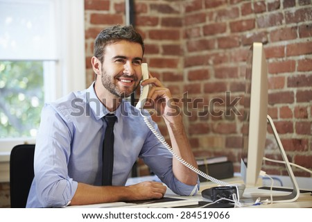 Man Working At Computer In Contemporary Office - stock photo