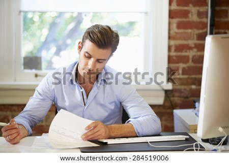 Man Working At Desk In Contemporary Office - stock photo