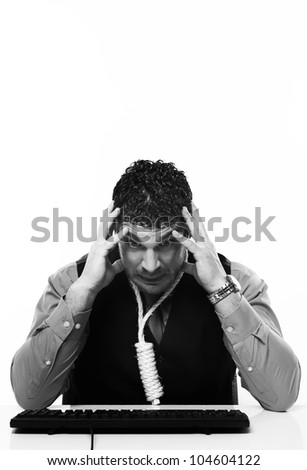 man working at his desk with a hangmans noose around his neck - stock photo