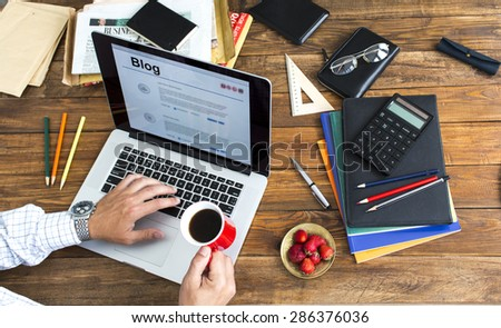 Man working at wooden desk.  Man typing on keyboard drinking coffee at wooden desk with laptop newspaper magazines and plate of strawberry - stock photo