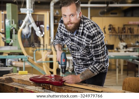 Man working at workshop with guitar - stock photo