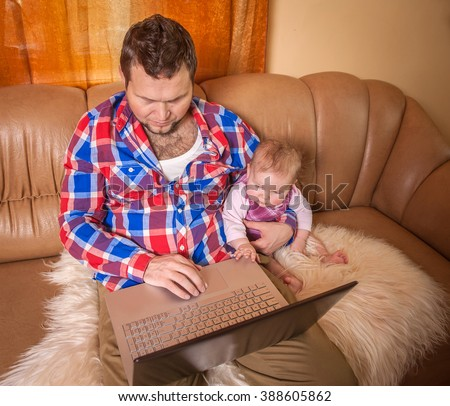 Man working from home and taking care of baby - stock photo