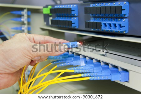 man working in network server room with fiber optic hub for digital communications and internet - stock photo